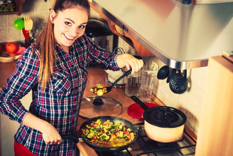 Donna che frigge le verdure congelate Frittura di scalpore fotografia stock libera da diritti