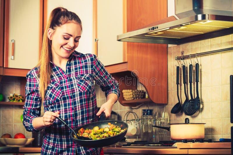 Donna che frigge le verdure congelate Frittura di scalpore immagine stock