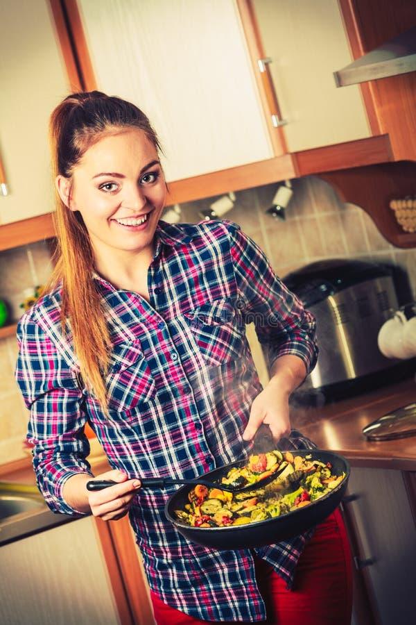 Donna che frigge le verdure congelate Frittura di scalpore immagini stock libere da diritti