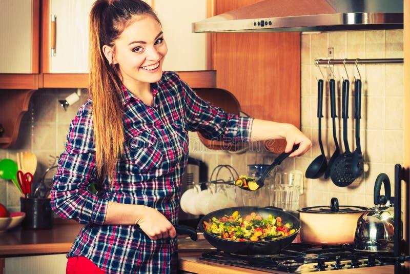 Donna che frigge le verdure congelate Frittura di scalpore fotografia stock