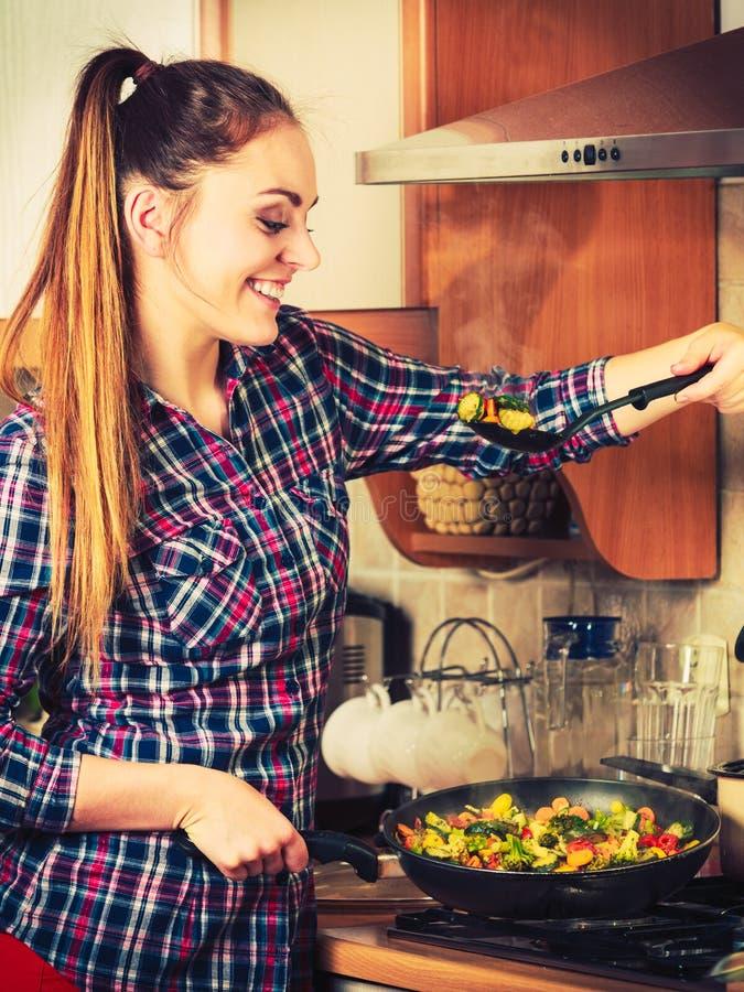 Donna che frigge le verdure congelate Frittura di scalpore fotografie stock