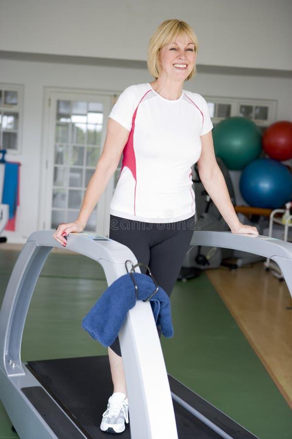 Donna che funziona sulla pedana mobile alla ginnastica fotografie stock