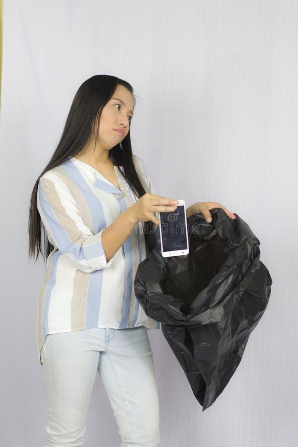 Donna che getta il suo telefono nella borsa di immondizia, posare isolata su fondo grigio fotografia stock