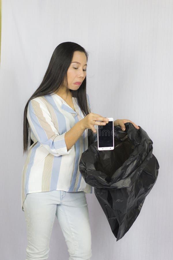 Donna che getta il suo telefono nella borsa di immondizia, posare isolata su fondo grigio fotografie stock libere da diritti