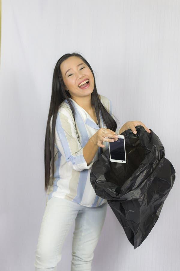 Donna che getta il suo telefono nella borsa di immondizia, posare isolata su fondo grigio immagine stock libera da diritti