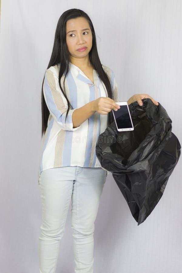 Donna che getta il suo telefono nella borsa di immondizia, posare isolata su fondo grigio immagine stock