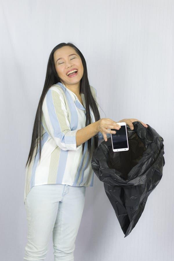 Donna che getta il suo telefono nella borsa di immondizia, posare isolata su fondo grigio fotografia stock libera da diritti