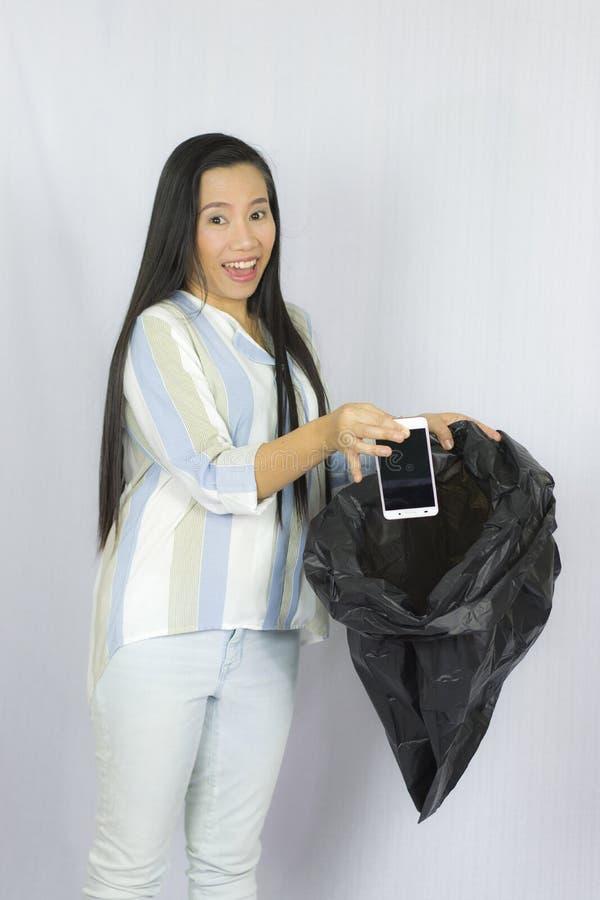 Donna che getta il suo telefono nella borsa di immondizia, posare isolata su fondo grigio immagini stock