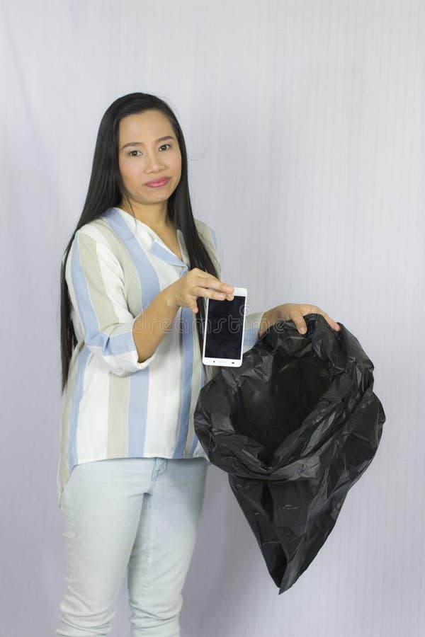 Donna che getta il suo telefono nella borsa di immondizia, posare isolata su fondo grigio immagini stock libere da diritti