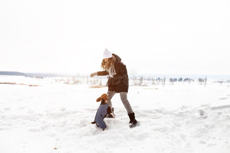 Donna che gioca con il cane da lepre del cane all'aperto su neve nel giorno di inverno soleggiato immagini stock