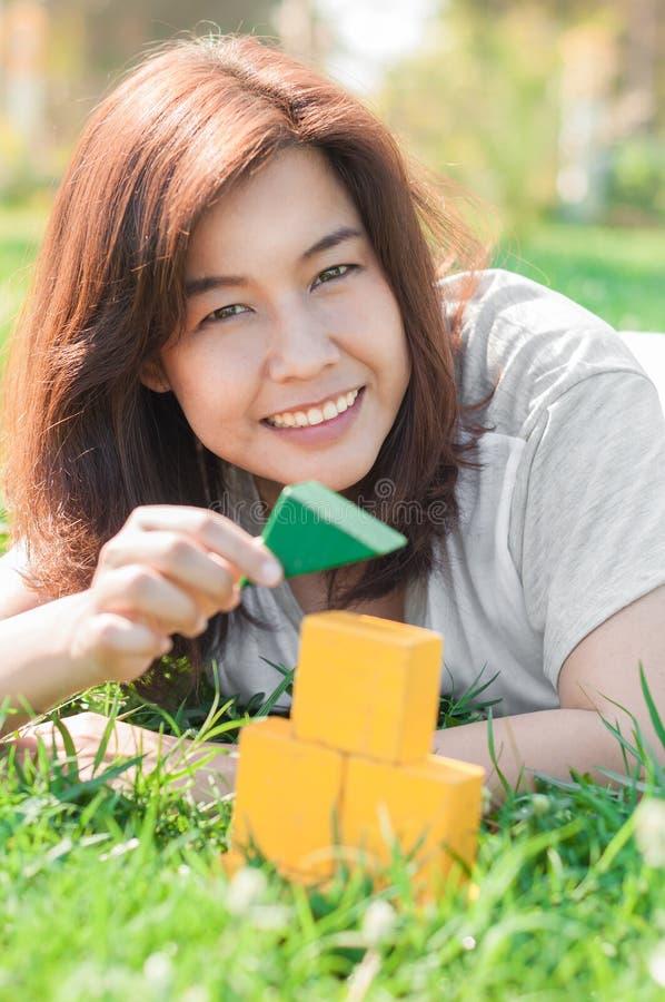 Donna che gioca il mini modello della casa nel giardino fotografia stock libera da diritti