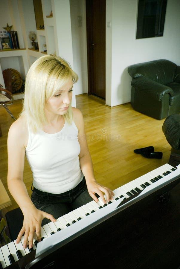 Donna che gioca il piano fotografia stock
