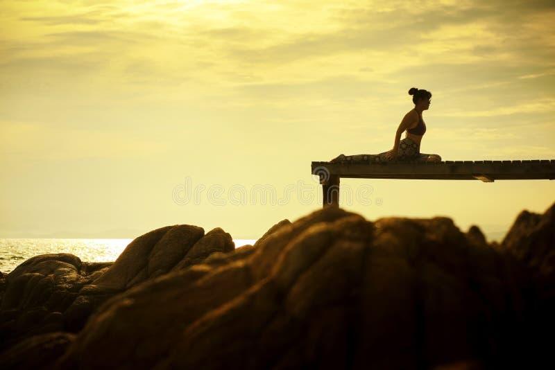 Donna che gioca posa di yoga sul pilastro della spiaggia contro il bello risi del sole fotografia stock libera da diritti