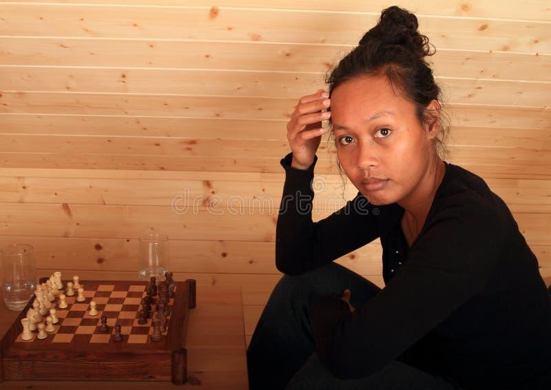 Donna che gioca scacchi immagine stock