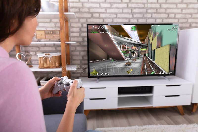 Donna che gioca video gioco con la leva di comando immagini stock