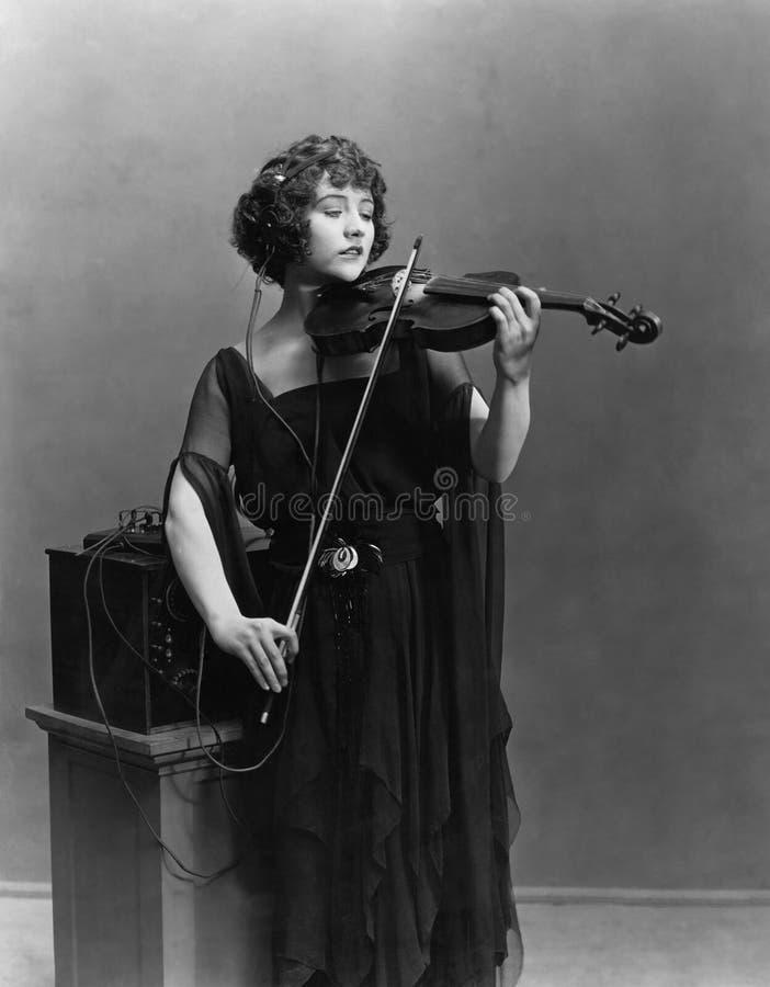 Donna che gioca violino con le cuffie fotografia stock libera da diritti