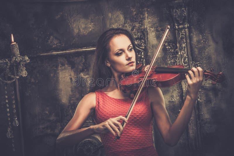 Donna che gioca violino nell'interno mistico immagini stock