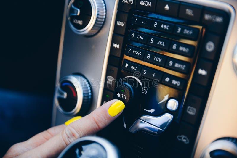 Donna che gira sul modo automatico sul condizionatore d'aria automatico dell'automobile immagini stock libere da diritti