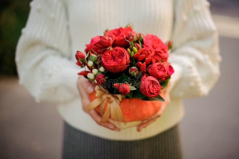 Donna che giudica una zucca decorata con i fiori rossi immagine stock