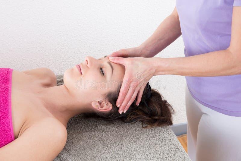 Donna che gode del massaggio capo nel rilassamento di trattamento di agopressione e nella medicina alternativa fotografie stock libere da diritti