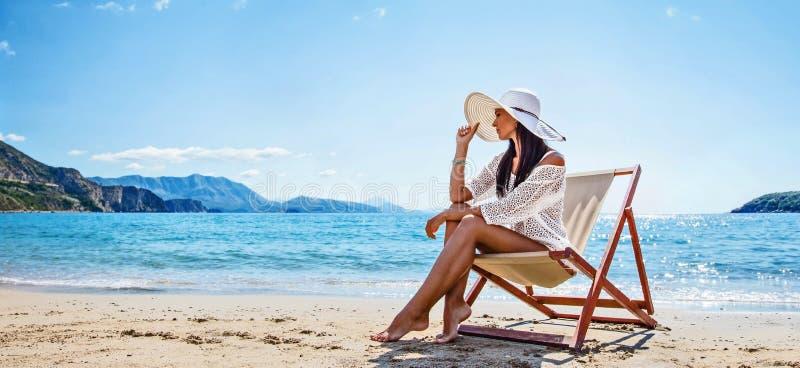 Donna che gode del prendere il sole alla spiaggia immagini stock libere da diritti