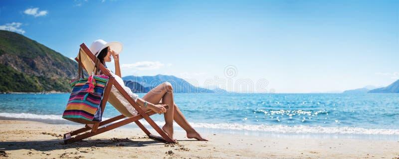 Donna che gode del prendere il sole alla spiaggia fotografia stock libera da diritti