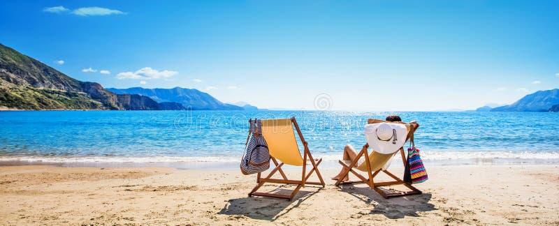 Donna che gode del prendere il sole alla spiaggia fotografia stock