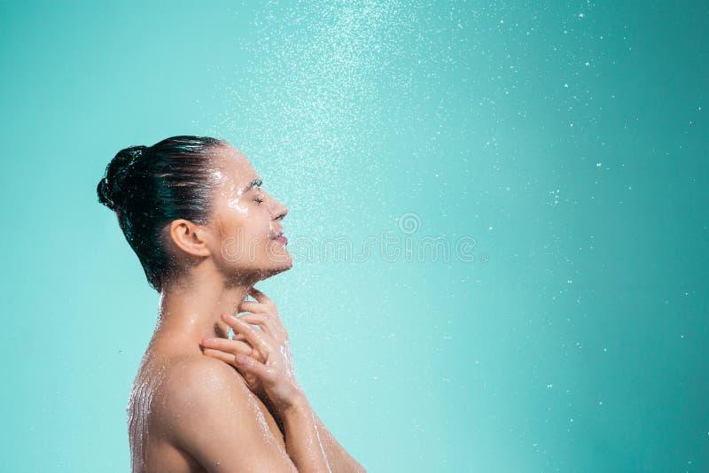 Donna che gode dell'acqua nella doccia sotto un getto fotografia stock