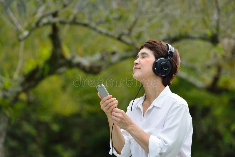 Donna che gode della musica dallo smartphone immagine stock