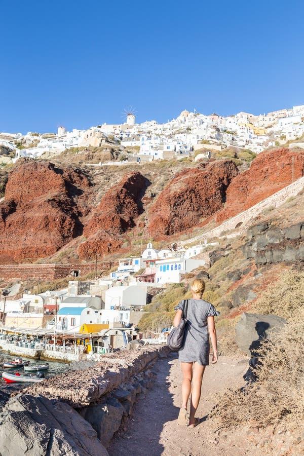 Donna che gode delle vacanze al villaggio di fama mondiale di OIA o a Ia, isola di Santorini, Grecia fotografie stock libere da diritti