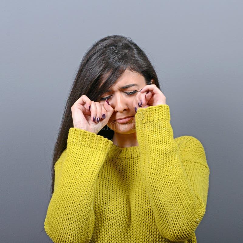 Donna che grida e che pulisce gli strappi contro il fondo grigio immagini stock