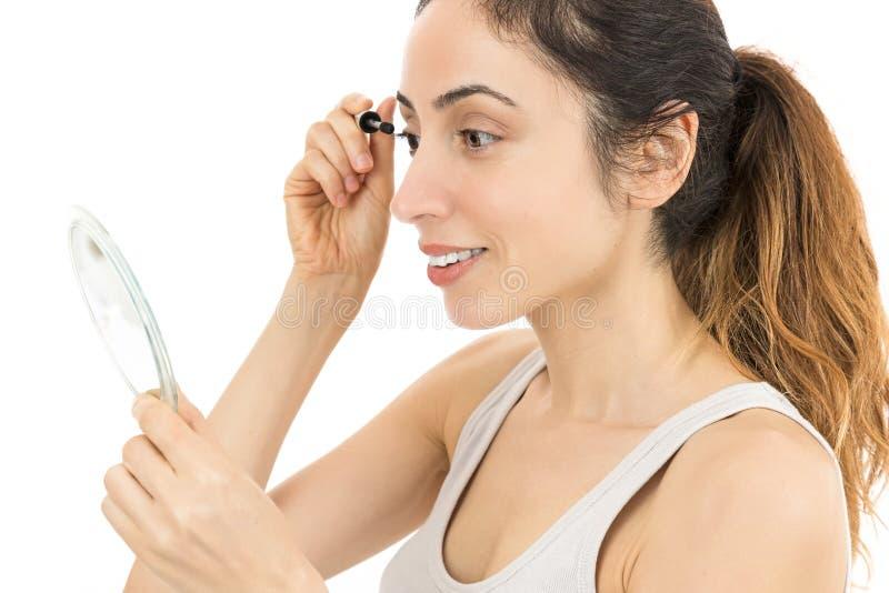 Donna che guarda allo specchio e che applica mascara immagine stock