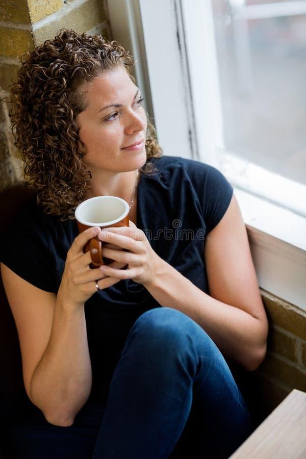 Donna che guarda attraverso la finestra in caffè immagini stock