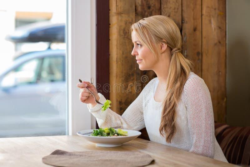 Donna che guarda attraverso la finestra mentre mangiando insalata immagini stock