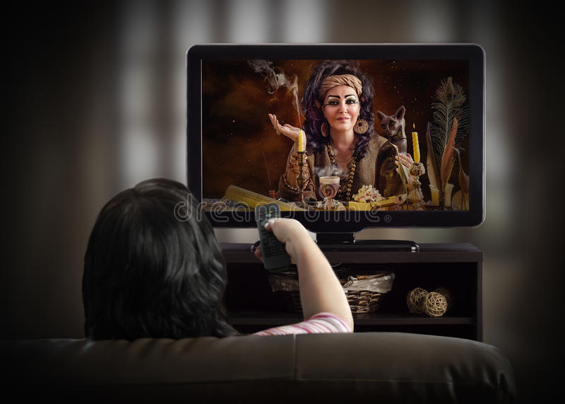 Donna che guarda canale televisivo esoterico su uno strato fotografia stock