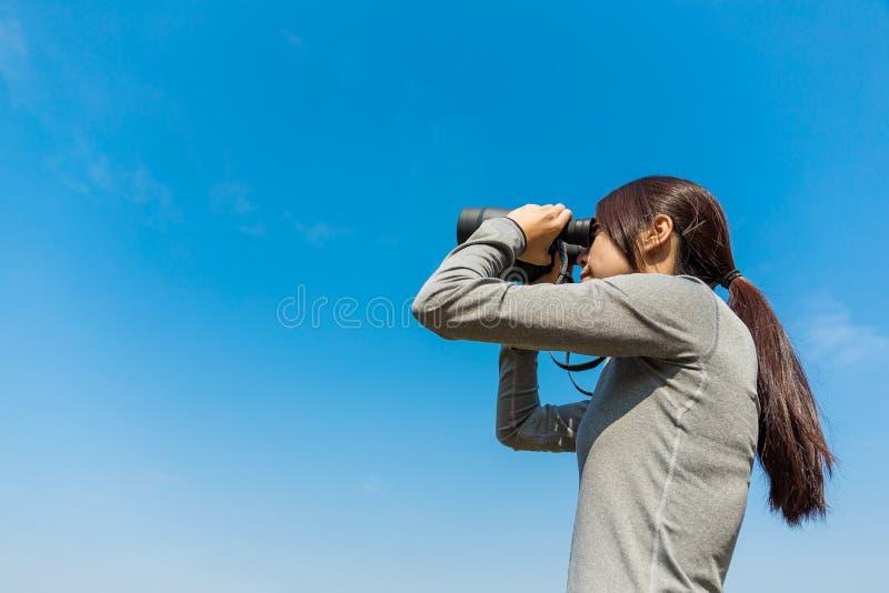 Donna che guarda comunque il binocolo fotografie stock libere da diritti