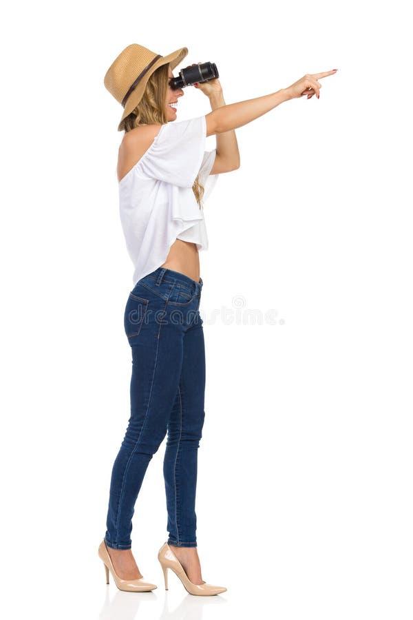 Donna che guarda con il binocolo ed indicare fotografia stock