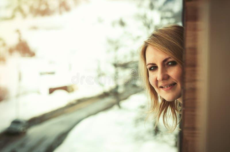 Donna che guarda dalla finestra fotografia stock