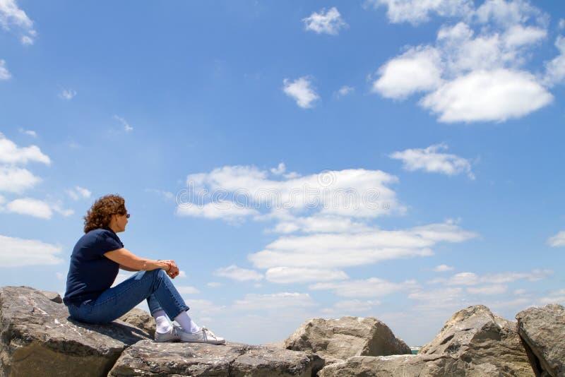 Donna che guarda dalle rocce immagine stock libera da diritti
