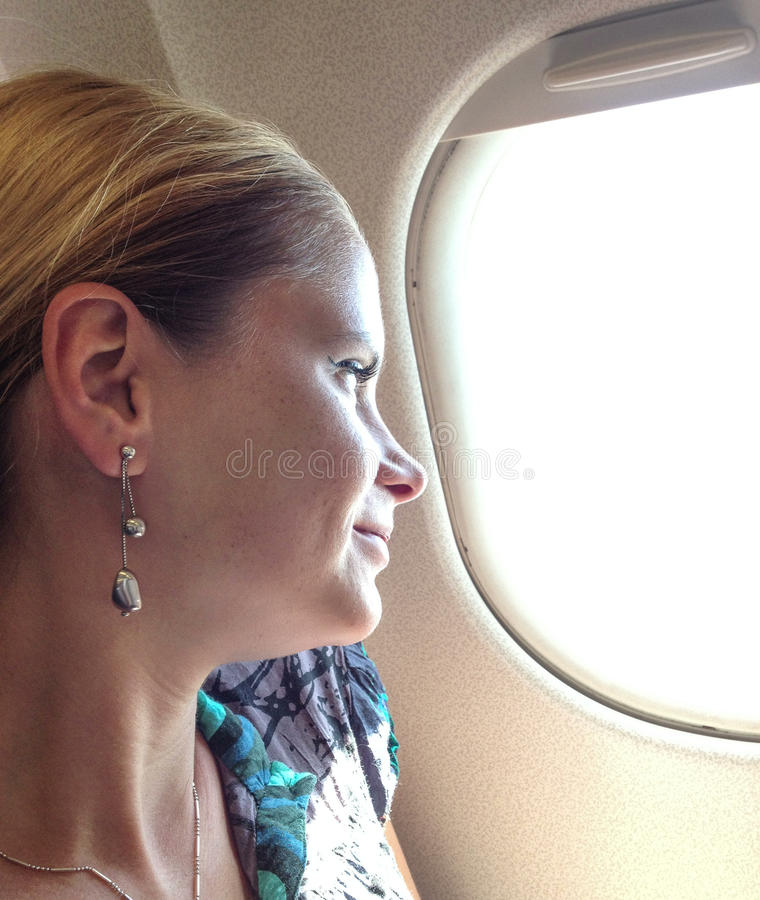 Donna che guarda fuori la finestra dell'aeroplano fotografie stock libere da diritti