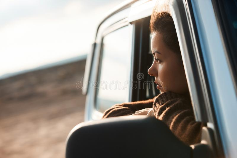 Donna che guarda fuori la finestra della sua automobile immagini stock