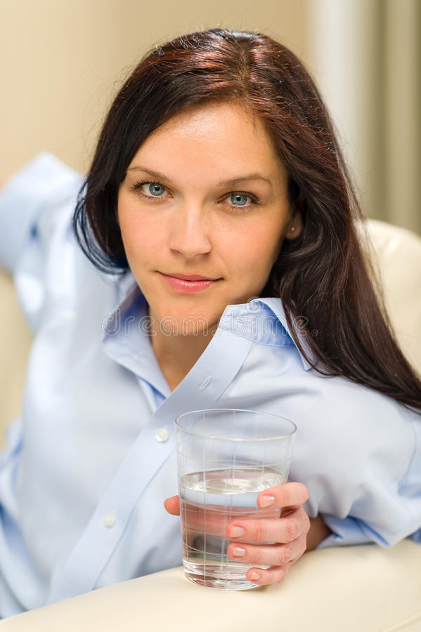 Donna che guarda macchina fotografica che tiene bicchiere d'acqua immagine stock libera da diritti