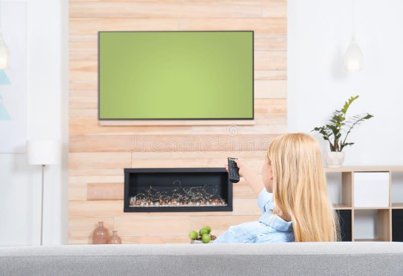 Donna che guarda TV sul sofà nella sala con il camino decorativo fotografia stock libera da diritti