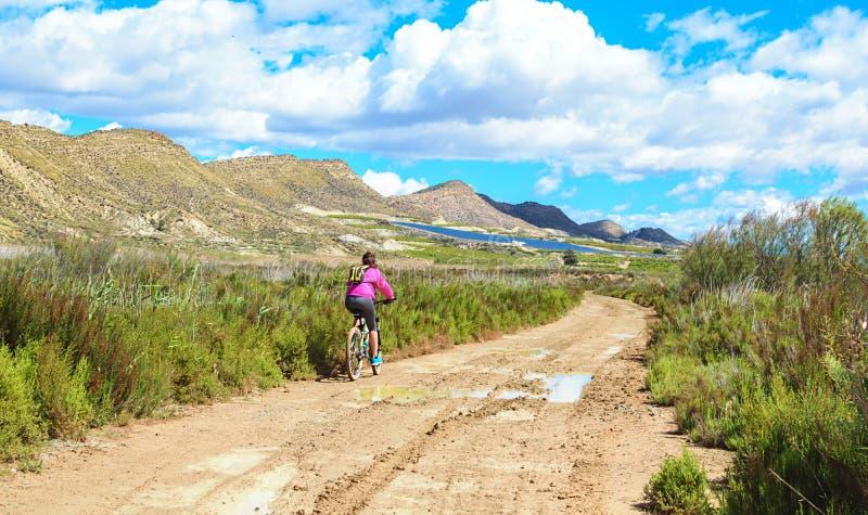 Donna che guida un mountain bike da un percorso fangoso di sporcizia fotografia stock libera da diritti