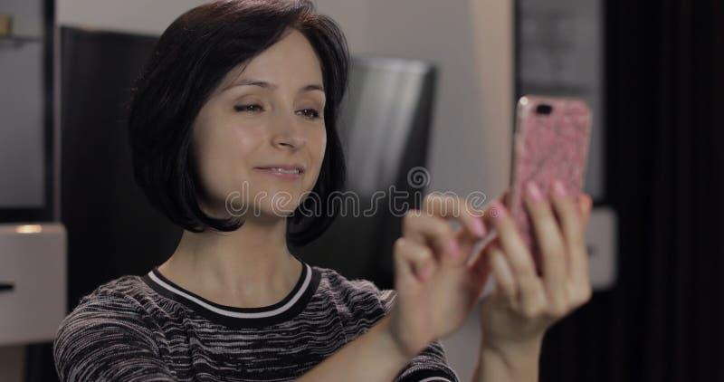 Donna che ha chiacchierata sui media sociali facendo uso dello smartphone che gode della chiacchierata all'amico immagini stock libere da diritti