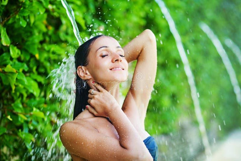 Donna che ha doccia sotto la cascata tropicale immagine stock libera da diritti