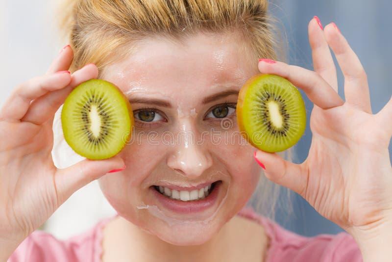 Donna che ha maschera del gel sul kiwi della tenuta del fronte immagine stock
