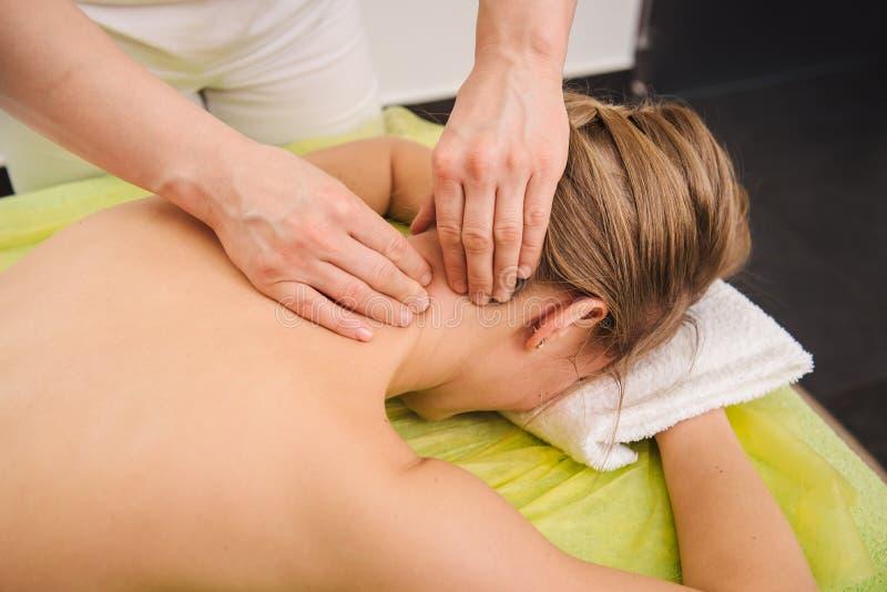 Donna che ha massaggio della spalla e del collo nel centro della stazione termale fotografie stock libere da diritti