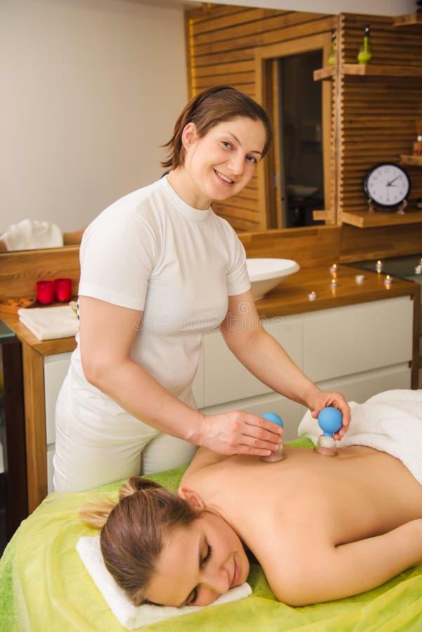 Donna che ha massaggio foggiante a coppa di vuoto caldo del barattolo nel centro della stazione termale immagini stock