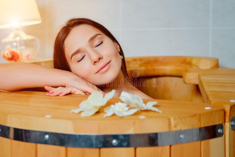 Donna che ha trattamento della stazione termale e che si rilassa nella sauna calda di legno del barilotto, vasca del cedro immagine stock